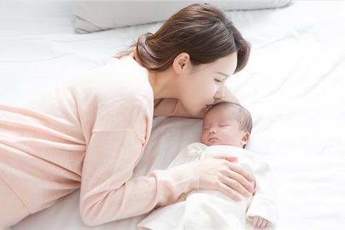 握住新生儿双下腿,单腿交换,将膝关节弯曲到90度贴于宝宝腹部,再将腿